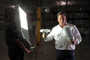 In the company's Fort Lauderdale warehouse, CEO Daniel Gold holds some of the light fixtures installed by Future Energy Solutions. (PHOTO CREDIT: CHARLES TRAINOR JR.)