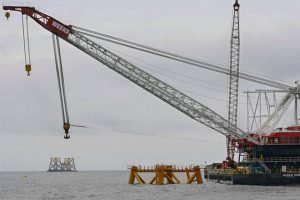 In this July 27, 2015 file photo, a construction crane works over a foundation installed for a wind turbine by Deepwater Wind off the coast of Block Island. (Stephan Savoia, File AP Photo)